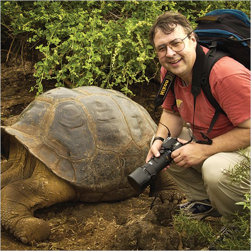Don Johnston next to a large tortoise